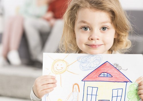 Girl holding picture of house drawing